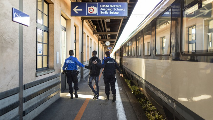 ZUR ARBEIT DER GRENZWACHE STELLEN WIR IHNEN HEUTE FOLGENDES NEUES BILDMATERIAL ZUR VERFUEGUNG --- Members of the Swiss Border Guard Corps accompany an asylum seeker who entered Switzerland by train without papers to take his personal data and to question him about his reasons of entry, pictured at the train station at the Swiss-Italian border in Chiasso, Switzerland, on October 23, 2014. (KEYSTONE/Gaetan Bally)