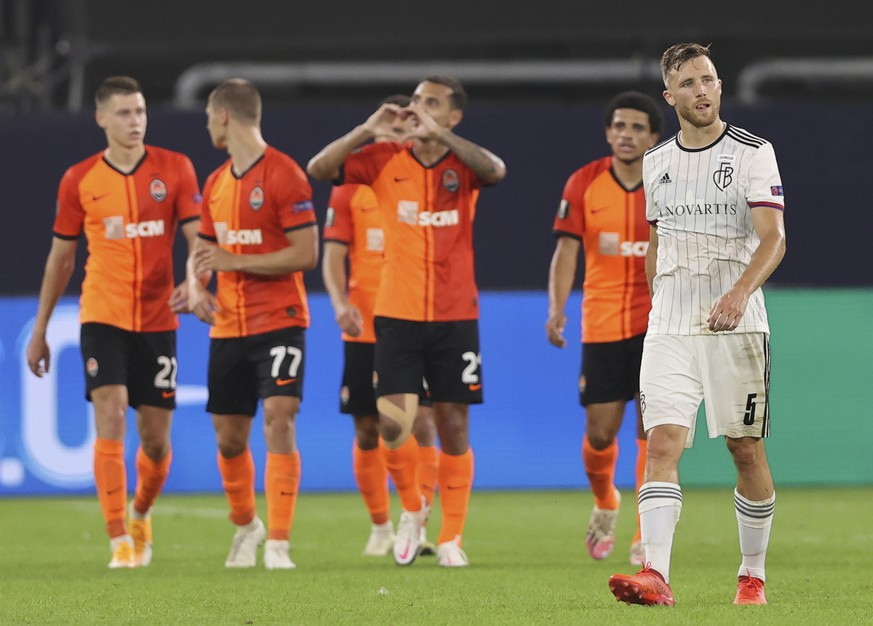 epa08598105 Silvan Widmer of Basel (R) reacts while Shakhtar players celebrate a goal during the UEFA Europa League quarter final match between Shakhtar Donetsk and FC Basel in Gelsenkirchen, Germany, 11 August 2020.  EPA/Wolfgang Rattay / POOL