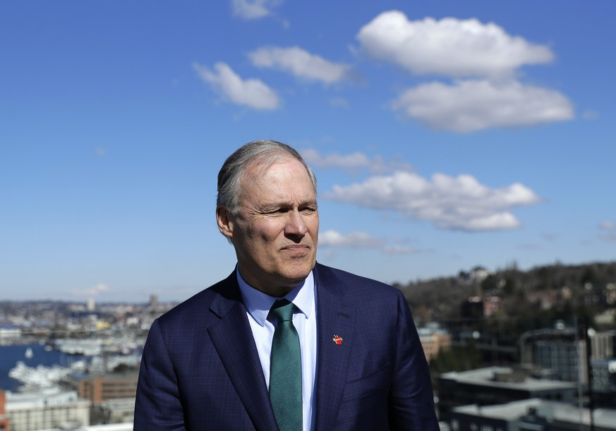 In this March 1, 2019 photo, Washington Gov. Jay Inslee stands on an outdoor patio as he takes part in media interviews in Seattle after announcing earlier in the day that he will seek the 2020 Democratic presidential nomination. Inslee, who made fighting climate change the central theme of his presidential campaign, announced Wednesday night, Aug. 21, 2019, that he is ending his bid for the 2020 Democratic nomination. Inslee announced his decision on MSNBC, saying it's become clear that he won't win. (AP Photo/Ted S. Warren) Jay Inslee