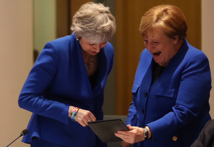 epa07497087 Britain's Prime minister Theresa May (L) and Germany's Chancellor Angela Merkel (R) look at a tablet ahead of a European Council meeting on Brexit at the European Council in Brussels, Belgium, 10 April 2019. EU leaders gathered for an emergency summit in Brussels to discuss a new Brexit extension.  EPA/KENZO TRIBOUILLARD / POOL  MAXPPP OUT