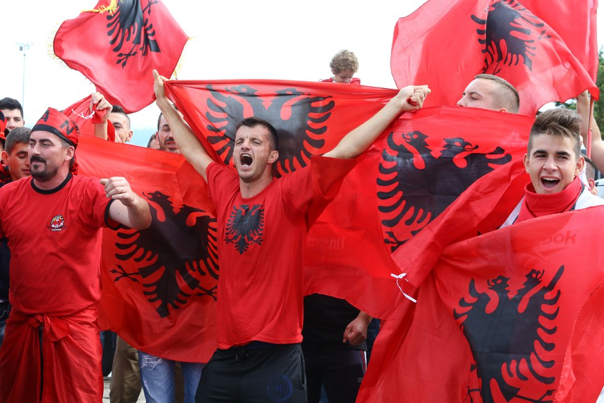 Albanian soccer fans shout slogans as they wait for the arrival of their national soccer team in Tirana, Monday, Oct. 12, 2015. Albania beat Armenia on Sunday and qualified for the European Soccer Championship in France next summer for first time. (AP Photo/Hektor Pustina)