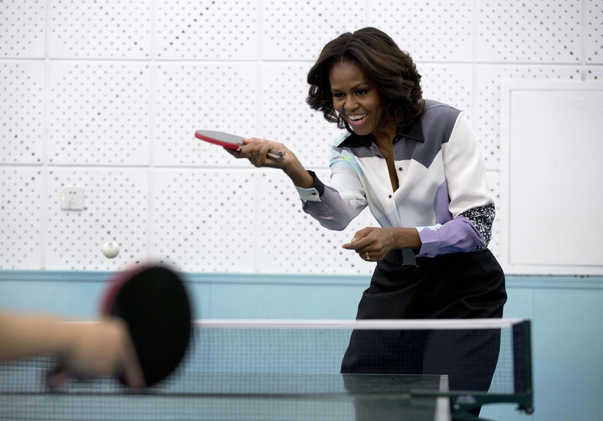 U.S. first lady Michelle Obama plays table tennis during her visit of Beijing Normal School, a school that prepares students for universities abroad, in Beijing March 21, 2014. REUTERS/Andy Wong/Pool (CHINA - Tags: POLITICS TPX IMAGES OF THE DAY SPORT TABLE TENNIS)