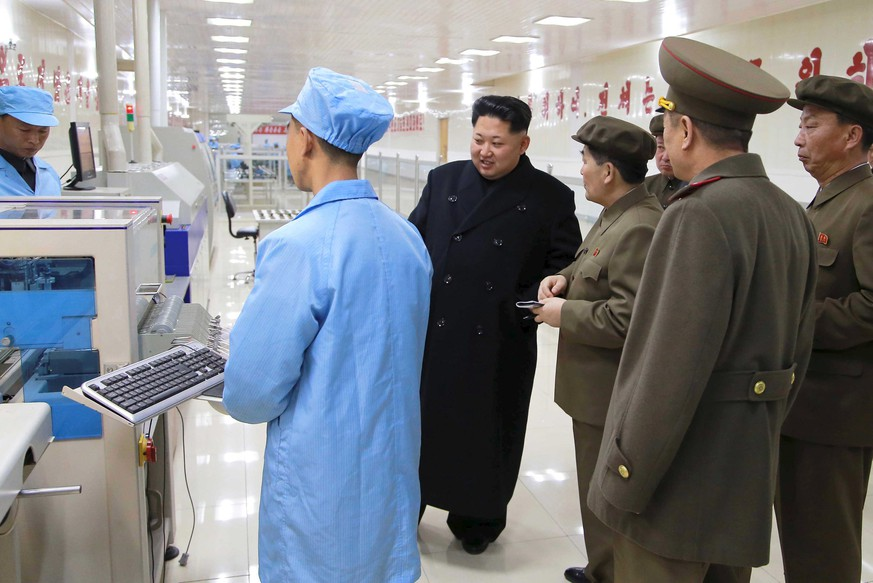 North Korean leader Kim Jong Un (C) looks on during a visit to the Pyongyang Weak-current Machine Plant, in this undated photo released by North Korea's Korean Central News Agency (KCNA) in Pyongyang on April 8, 2015.    REUTERS/KCNA  