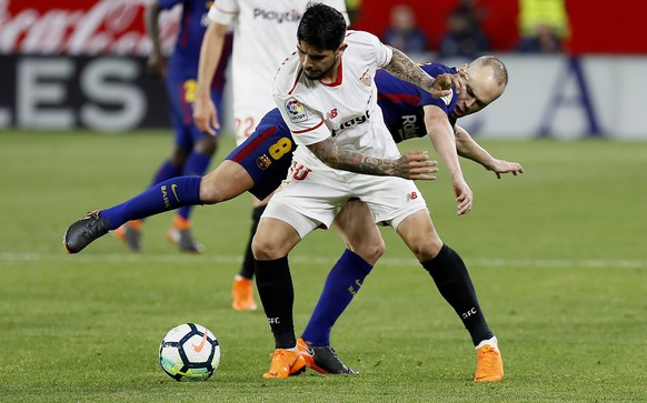 epa06639582 Sevilla CF's Ever Banega (front) duels for the ball with FC Barcelona's Andres Iniesta (rear) during their Spanish Liga Primera Division soccer match played at Ramon Sanchez Pizjuan stadium, in Seville, Spain, 31 March 2018.  EPA/Jose Manuel Vidal