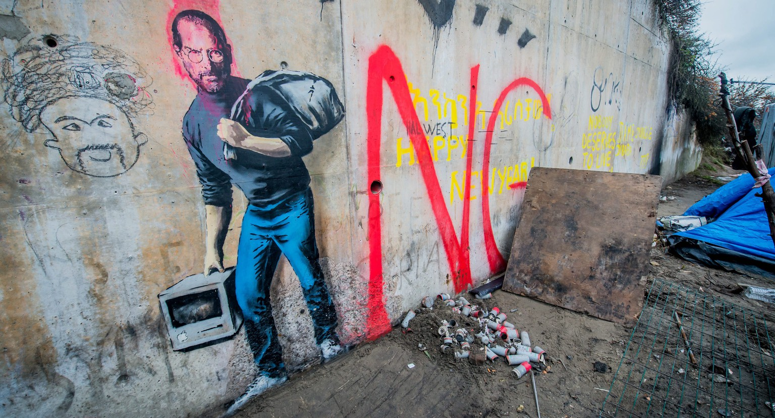 epa05080941 A tag of the artist Banksy representative Steve Jobs in the camp called 'The Jungle' in the port of Calais, France, 25 December 2015.  By this Banksy tag means that Steve Jobs was also a Syrian migrant son come Holms. He said.