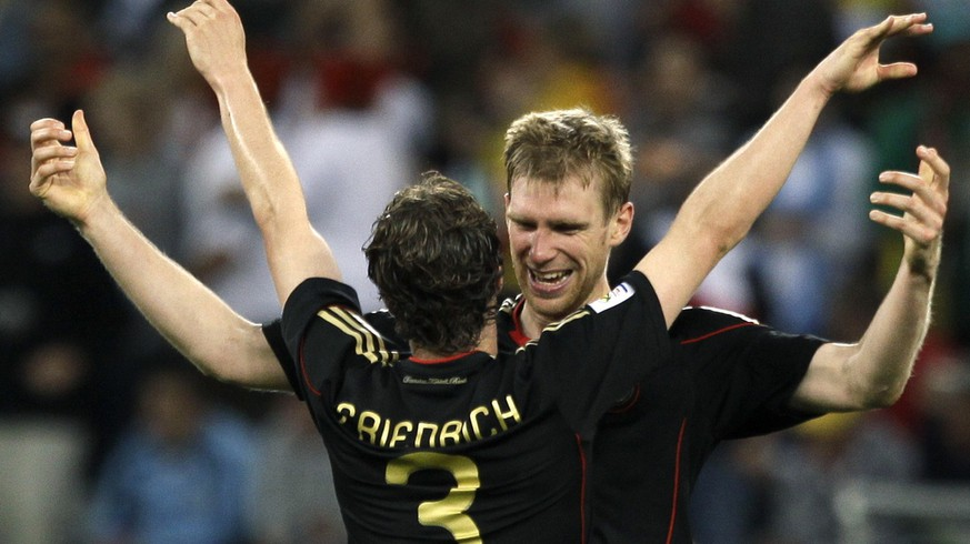 Germany's Arne Friedrich, left, celebrates with teammate Per Mertesacker after their teammate Miroslav Klose scored their side's fourth goal during the World Cup quarterfinal soccer match between Argentina and Germany at the Green Point stadium in Cape Town, South Africa, Saturday, July 3, 2010.  Germany won 4-0. (AP Photo/Julie Jacobson)