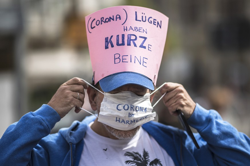 epa08382459 A participant puts on a protective face mask reading 'Corona is harmless' as he wears a sign reading '(Corona) Lies have short legs' referring to Austrian Chancellor Sebastian Kurz during a demonstration against the measures of the Austrian government to slow down the ongoing pandemic of the COVID-19 disease caused by the SARS-CoV-2 coronavirus in Vienna, Austria, 24 April 2020.  EPA/CHRISTIAN BRUNA
