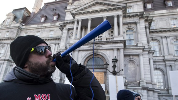 A city worker blows his horn in front of city hall during a demonstration of city workers unions and firemen in support of their contract negotiations Monday, March 23, 2015, in Montreal. (AP Photo/The Canadian Press, Paul Chiasson)