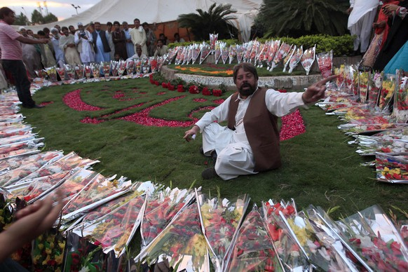 Pakistani Christian peace activist Julius Salik gestures while sitting in flower bouquets for anti-government protesters to show solidarity with them during the Revolution March in Islamabad September 3, 2014. Pakistan's protest leaders demanding Prime Minister Nawaz Sharif's resignation prepared to resume talks with the government on Wednesday, reviving hopes for a negotiated solution to a crisis that has shaken the coup-prone nation. REUTERS/Akhtar Soomro (PAKISTAN - Tags: POLITICS CIVIL UNREST)