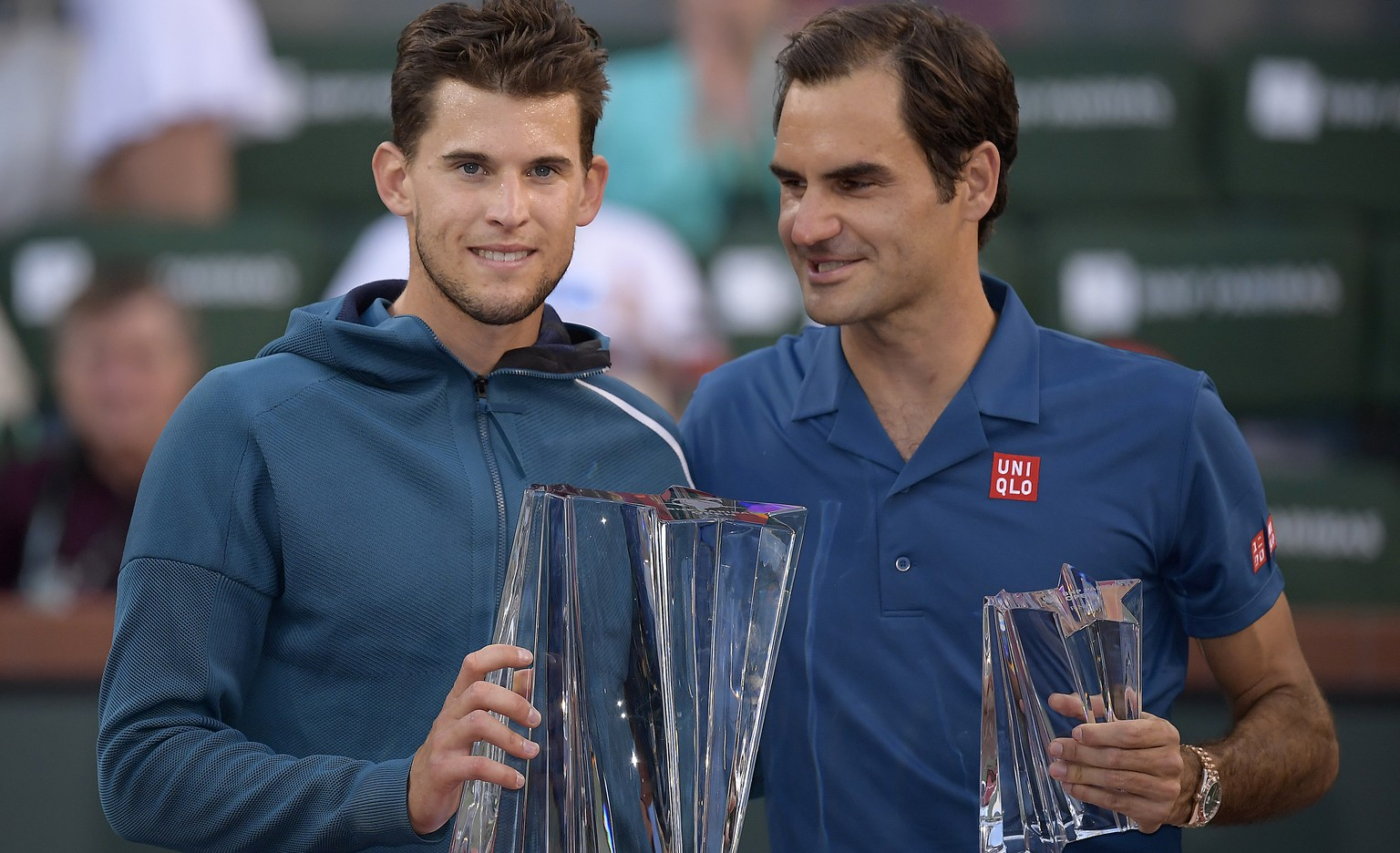 Dominic Thiem, of Austria, left, and Roger Federer, of Switzerland, pose with trophies after Thiem defeated Federer in the men's final at the BNP Paribas Open tennis tournament Sunday, March 17, 2019, in Indian Wells, Calif. Thiem won 3-6, 6-3, 7-5. (AP Photo/Mark J. Terrill)