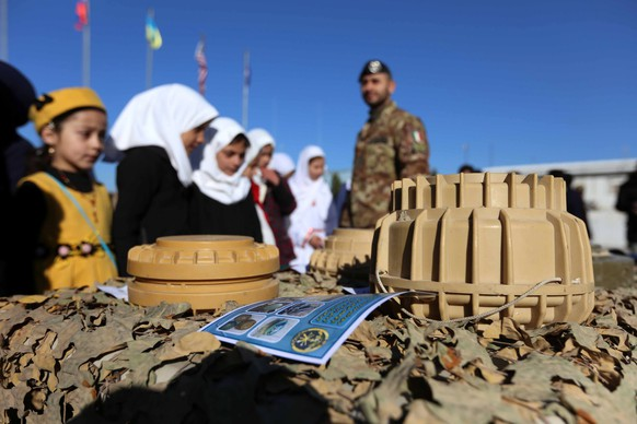 epa06359737 Afghan and Italian soldiers of NATO's Resolute Support Mission shows the preventative measures about landmines during a workshop for Afghan students in Herat, Afghanistan, 30 November 2017. After almost three decades of war, the countless numbers of mines that remain buried in Afghanistan still kill or maim more than dozens of people every month.  EPA/JALIL REZAYEE