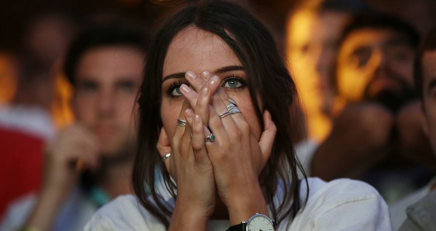 An England soccer fans reacts after Croatia scored their side's second goal as she watches a live broadcast on a big screen of the semifinal match between Croatia and England at the 2018 soccer World Cup, in Flat Iron Square, south London, Wednesday, July 11, 2018. (AP Photo/Luca Bruno)