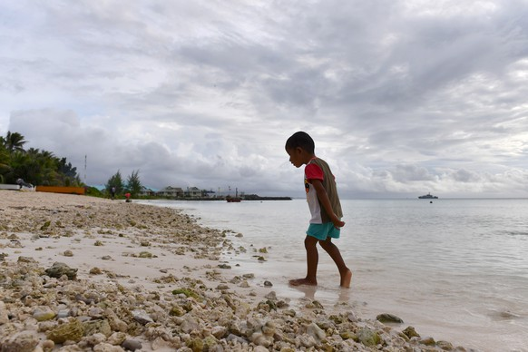 epa07770649 A child walks along the shore of the lagoon in Funafuti, Tuvalu, 13 August 2019. The 50th Pacific Islands Forum and Related Meetings, fostering cooperation between governments comprising 18 countries in the region, run from 13 to 16 August 2019 in Tuvalu.  EPA/MICK TSIKAS  AUSTRALIA AND NEW ZEALAND OUT