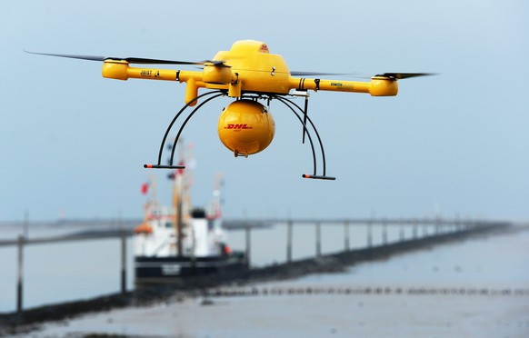 epa04494493 German parcel service DHL's 'Paketkopter' (lit.: 'parcel copter') drone delivery service begins its flight with medicine over to the island of Juist from Norddeich, Germany, 18 November 2014. After the successful transport of urgent and needed goods to an island using a drone, this unique project was officially demonstrated for the media.  EPA/INGO WAGNER
