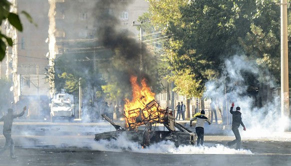 Kurdish protestors clash with Turkish riot policemen in the southeastern city of Diyarbakir on October 7, 2014. Fresh air strikes by the US-led coalition hit positions held by Islamic State jihadists in the southwest of the key Syrian border town of Ain al-Arab (Kobane), according to an AFP journalist just across the border in Turkey. The strikes came a day after the extremists pushed into Kobane, seizing three districts in the city's east after fierce street battles with its Kurdish defenders. AFP PHOTO / ILYAS AKENGIN