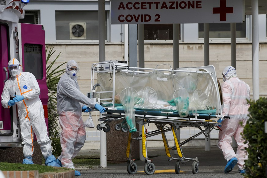 A patient in a biocontainment unit is carried on a stretcher from an ambulance arrived at the Columbus Covid 2 Hospital in Rome, Tuesday, March 17, 2020.  For most people, the new coronavirus causes only mild or moderate symptoms. For some it can cause more severe illness, especially in older adults and people with existing health problems. (AP Photo/Alessandra Tarantino)
