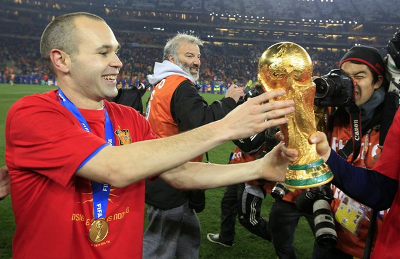 Spain's Andres Iniesta celebrates with the trophy after winning the 2010 FIFA soccer World Cup final between the Netherlands and Spain in the Soccer City Stadium in Johannesburg, South Africa, pictured on Sunday, July 11, 2010. (KEYSTONE/Peter Klaunzer)EDITOR'S NOTE: Under terms of the World Cup journalist accreditation agreement, images from World Cup soccer matches may only be displayed on mobile devices at the end user's initiative and request, unpromted by any alert, update or other information pushed to the user's device. No trademark rights or rights of personality are conveyed with these images. All usage must comply with FIFA credential restrictions posted at http://www.ap.org/mediacredential/index.html