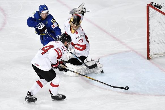 epa05972943 Switzerland's goaltender Leonardo Genoni (R) and Philippe Furrer (front) in action against Sweden's Oscar Lindberg during the IIHF Ice Hockey World Championship 2017 quarter final game between Switzerland and Sweden in Paris, France, 18 May 2017.  EPA/PETER SCHNEIDER