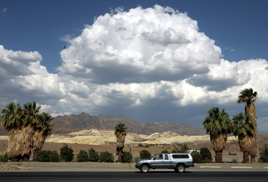 FILE - This July 22, 2005 file photo shows clouds over the Amargosa Range at Furnace Creek in Death Valley National Park in California's Mojave Desert. Located about two hours west of Las Vegas along the California-Nevada state line, Death Valley is unique. Part of the Mojave Desert, it is the lowest point in the Western Hemisphere, 282 feet below sea level at the salt flats of Badwater. (AP Photo/Reed Saxon, File)