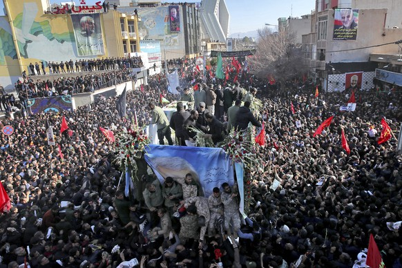 """Coffins of Gen. Qassem Soleimani and others who were killed in Iraq by a U.S. drone strike, are carried on a truck surrounded by mourners during a funeral procession, in the city of Kerman, Iran, Tuesday, Jan. 7, 2020. The leader of Iran's Revolutionary Guard threatened on Tuesday to """"set ablaze"""" places supported by the United States over the killing of a top Iranian general in a U.S. airstrike last week, sparking cries from the crowd of supporters of """"Death to Israel!"""" (Erfan Kouchari/Tasnim News Agency via AP)"""