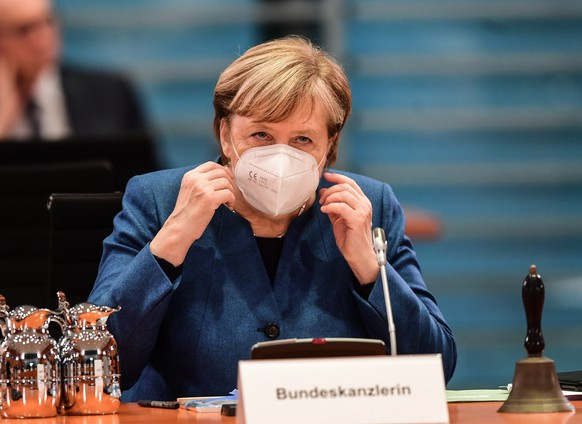 epa08779846 German chancellor Angela Merkel adjusts her mask on her face prior to the start of the weekly meeting of the German Federal Cabinet in Berlin, Germany, 28 October 2020.  EPA/FILIP SINGER / POOL