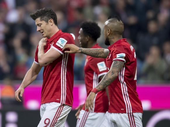 Bayern's Robert Lewandowski, left, holds his shoulder during the German Bundesliga soccer match between FC Bayern Munich and Borussia Dortmund in Munich, Germany, Saturday, April 8, 2017. (Sven Hoppe/dpa via AP)