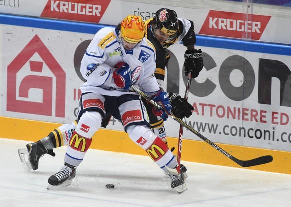 ZSC-Spieler Roman Wick, links, im Duell mit Luganos Lukas Balmelli, beim Eishockey Meisterschaftsspiel der National League A zwischen dem HC Lugano und den ZSC Lions, am Samstag, 11. Oktober 2014, in der Resega-Eishalle in Lugano. (PHOTOPRESS/Gabriele Putzu)