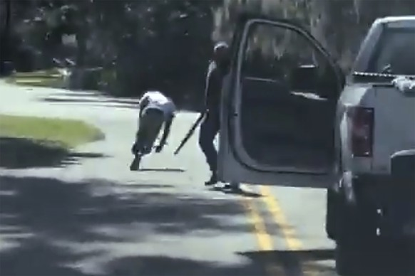 In this image from video posted on Twitter Tuesday, May 5, 2020, Ahmaud Arbery stumbles and falls to the ground after being shot as Travis McMichael stands by holding a shotgun in a neighborhood outside Brunswick, Ga., on Feb. 23, 2020. (Twitter via AP)