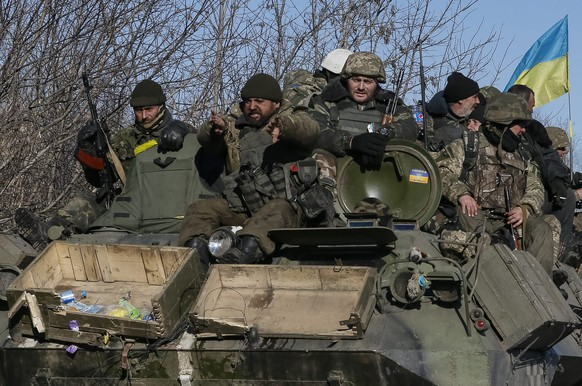 Ukrainian servicemen ride on a military vehicle as they leave an area around Debaltseve, eastern Ukraine near Artemivsk, February 18, 2015. Weary Ukrainian troops, some in columns, some in cars, began arriving on Wednesday from the besieged town of Debaltseve in Artemivsk, a Reuters witness said.  REUTERS/Gleb Garanich (UKRAINE - Tags: POLITICS CIVIL UNREST MILITARY CONFLICT)