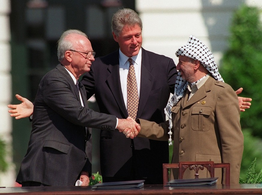 PLO leader Yasser Arafat, right, shakes hands with Israeli Prime Minister Yitzhak Rabin, left, under the glance of US President Bill Clinton, center, in Washington D.C. USA, September 13, 1993, after Arafat and Rabin signed a historic peace agreement.   (KEYSTONE/AP Photo/Ron Edmonds)