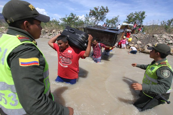 Colombian police watch people carry their household belongings across the Tachira River from Venezuela, top, to Colombia, on the border that separates San Antonio del Tachira, Venezuela from Villa del Rosario, Colombia, Tuesday, Aug. 25, 2015, during a mass exodus of Colombians. Venezuelan President Nicolas Maduro vowed to extend a crackdown on illegal migrants from neighboring Colombia he blames for rampant crime and widespread shortages, while authorities across the border struggled to attend to droves of returning deportees.  (AP Photo/Eliecer Mantilla)