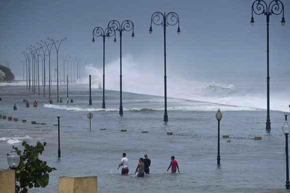 Residents walk on Havana's flooded sea wall as the ocean crashes into it, after the passing of Hurricane Irma in Havana, Cuba, Sunday, Sept. 10, 2017. The powerful storm ripped roofs off houses, collapsed buildings and flooded hundreds of miles of coastline after cutting a trail of destruction across the Caribbean.There were no immediate reports of deaths in Cuba, a country that prides itself on its disaster preparedness, but authorities were trying to restore power and clear roads. (AP Photo/Ramon Espinosa)