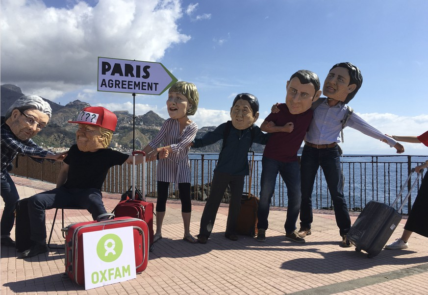 Oxfam activists wearing masks of the leaders of the G7 summit; from left, Italian Premier Paolo Gentiloni, US President Donald Trump, German Chancellor Angela Merkel, Japanese Prime Minister Shinzo Abe, French President Emmanuel Macron and Canadian Prime Minister Justin Trudeau, stage a demonstration in Giardini Naxos, near the venue of the G7 summit in the Sicilian town of Taormina, southern Italy, Friday, May 26, 2017. Climate change promises to be the most problematic issue for this summit after Trump's decision to review U.S. policies related to the Paris Agreement on fighting global warming. (AP Photo/Paolo Santalucia)