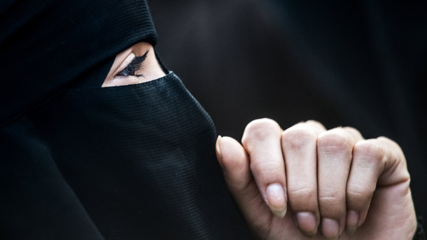 epaselect epa06238383 A protestor wears a niqab during a demonstration against a full-face veil ban in Vienna, Austria, 01 October 2017. The new law bans full-face veils in public places from 01 October 2017 on and says faces must be visible from the hairline to the chin. It bans burkas, niqabs, medical face masks or clown makeup.  EPA/CHRISTIAN BRUNA