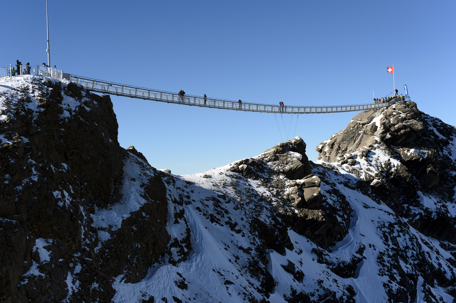 People walk on the bridge during the inauguration of the Peak Walk, the first and only suspension bridge to connect two mountain peaks, at the Glacier 3000 in Les Diablerets, Switzerland, Friday, 24 October, 2014. The Peak Walk connects the View Point peak with the main peak Scex Rouge (about 5 m higher). The 107 m long and 80 cm wide bridge offers a stunning view onto the Alps. (KEYSTONE/Laurent Gillieron)