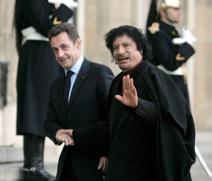 epa06615391 (FILE) - French President Nicolas Sarkozy (L) welcomes Libyan leader Muammar Gaddafi at Palais Elysee, Paris, France, 12 December 2007, (reissued 20 March 2018). Media reports on 20 March 2018 state that former French president is being questioned in connection to alleged Libyan financing for his 2007 election campaign.  EPA/MAYA VIDON
