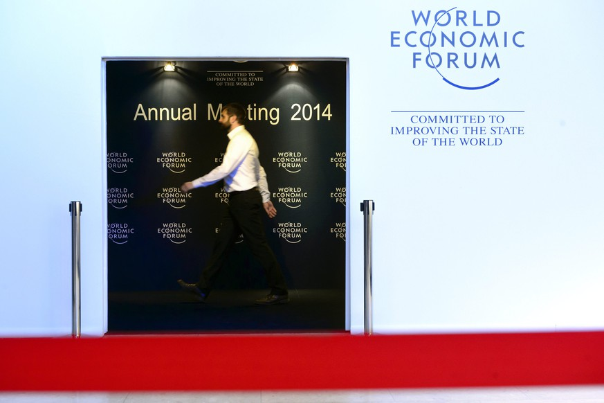 epa04040772 A participant walks inside the congress center on the last day of the 44th Annual Meeting of the World Economic Forum (WEF), in Davos, Switzerland, 25 January 2014. The overarching theme of the Meeting, which takes place from 22 to 25 January, is 'The Reshaping of the World: Consequences for Society, Politics and Business'.  EPA/LAURENT GILLIERON