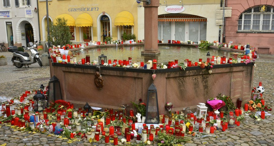 epa05634773 A well in a town square covered in flowers and letters of remembrance in honour of a recently murdered jogger in Endingen, Germany, 17 November 2016. Police investigations are underway after the body of a murdered 27-year-old jogger was found in the area.  EPA/WINFRIED ROTHERMEL