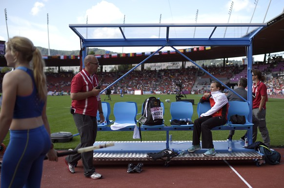 Nicole Buechler from Switzerland, right, sits on the bench as Patrick Magyar, left, CEO of the European Athletics Championships Zurich 2014, walks by, during the women's pole vault qualifying event at the first day of the European Athletics Championships in the Letzigrund Stadium in Zurich, Switzerland, Tuesday, August 12, 2014. (KEYSTONE/Ennio Leanza)