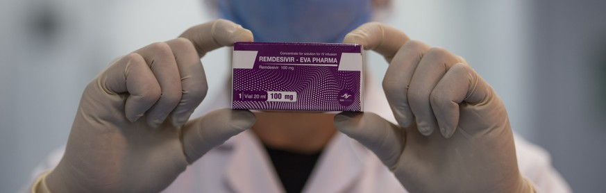 epa08508728 An employee wears a face mask and holds up a box of remdesivir while posing for a photograph at the laboratories of the Eva Pharma company in Cairo, Egypt, 25 June 2020. The Egyptian drugmaker has reached a landmark deal with US company Gilead Sciences Inc. licensing the former to manufacture Gilead's antiviral drug remdesivir ? an experimental treatment for patients suffering from the pandemic COVID-19 disease caused by the SARS-CoV-2 coronavirus ? and distribute it in 127 countries.  EPA/MOHAMED HOSSAM
