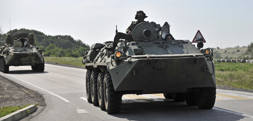 Two Russian armored personal carriers roll near the border with Ukraine outside the Russian town of Donetsk in Rostov-on-Don region, Sunday, July 13, 2014. Russia's foreign ministry said Sunday that a Ukrainian shell hit a town on the Russian border, killing one person and seriously injuring two others. But Ukraine denied firing a shell into Russian territory. (AP Photo/Sergei Pivovarov)