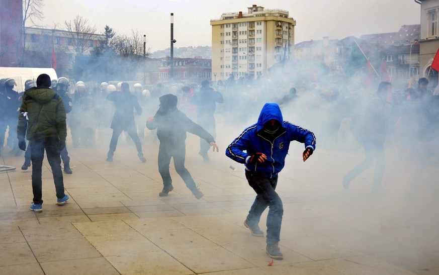epa04588787 Kosovo police officers fire tear gas during clashes at a demonstration in Pristina, Kosovo, 27 January 2015. Police in Kosovo used water cannons and tear gas to disperse the second violent anti-government demonstration within a week. The demonstrators, led by the opposition Vetevendosje party, are demanding the resignation of Aleksandar Jablanovic, a cabinet minister representing the Serb minority. Jablanovic had triggered outrage among local Albanians after describing those who had attacked Serb returnees as 'savages.'  EPA/STRINGER