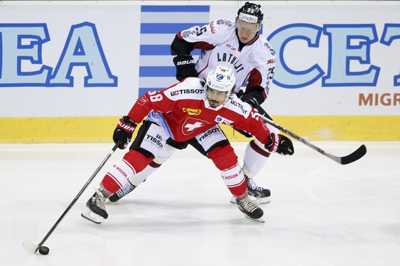 Switzerland's Eric Blum, left, vies for the puck with Latvia's Andris Dzerins, right, during friendly ice hockey game between Switzerland and Latvia, at the ice stadium Les Vernets, in Geneva, Switzerland, Friday, April 29, 2016. (KEYSTONE/Salvatore Di Nolfi)