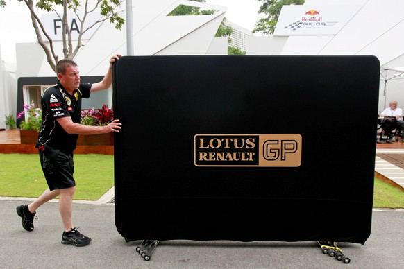 epa04931900 (FILE) A file picture dated 22 September 2011 of a Lotus Renault mechanic pushing a board along the paddock at the Marina Bay Street Circuit in Singapore, prior to the Singapore Formula One Grand Prix. French car manufacturer Renault's CEO Carlos Ghosn hat confirmed on 15 September 2015 that the company's days as Formula One engine supplier are over, media reports stated. Renault confirmed it is in renegotiations on its contract with Red Bull, questioning the Formula One team's sportsmanship.  EPA/DIEGO AZUBEL *** Local Caption *** 50051163