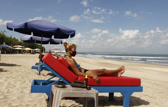 FILE - In this July 27, 2020, file photo, a tourist wearing face sunbathe as beaches are gradually reopening following months of lockdown due to the new coronavirus outbreak, in Bali, Indonesia. Indonesia said Monday, Oct. 4, 2021, that it plans to reopen the airport in the resort island of Bali for international flights on Oct. 14, after closing it for more than a year because of the COVID-19 pandemic. (AP Photo/Firdia Lisnawati, File)