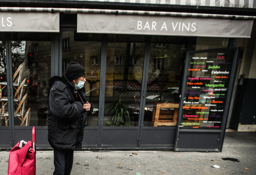 epa08811989 An elderly man wearing a face mask, stands next to a closed restaurant, in Paris, France, 10 November 2020. France re-intoduced lockdown measures in the midst of a second wave of the COVID-19 coronavirus pandemic.  EPA/MOHAMMED BADRA