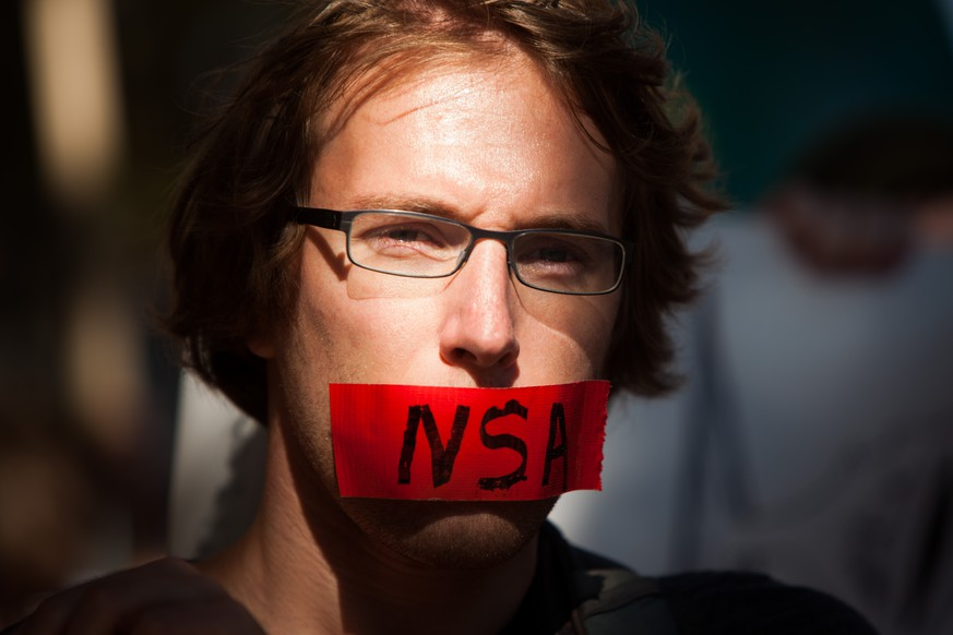 WASHINGTON, DC - OCTOBER 26, 2013:  A protester marches with a piece of tape covering his mouth during the Stop Watching Us Rally protesting surveillance by the U.S. National Security Agency, on October 26, 2013, in front of the U.S. Capitol building in Washington, D.C.  The rally began at Union Station and included a march that ended in front of the U.S. Capitol building and speakers such as author Naomi Wolf and former senior National Security Agency senior executive Thomas Drake. (Photo by Allison Shelley/Getty Images)