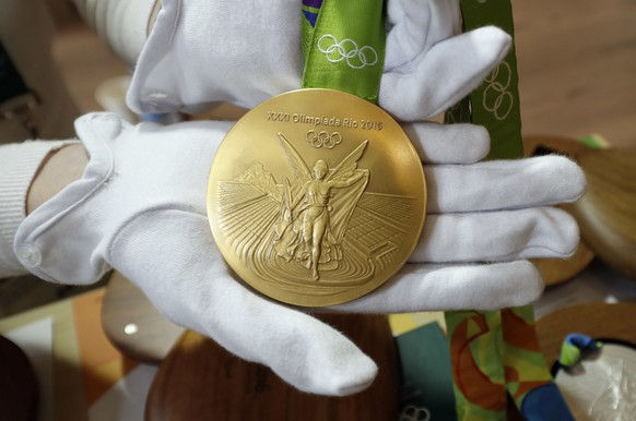 A Rio 2016 Olympic gold medal is displayed at the Olympic Park Wednesday, July 20, 2016, in Rio de Janeiro. There's no such thing as a gold medal, not at these upcoming Rio Olympics, and really, not ever. Second-place finishers get silver medals and oddly enough, so do the winners, albeit theirs are plated in a tiny amount of gold. The medals are largely made with recycled materials. (AP Photo/David J. Phillip)