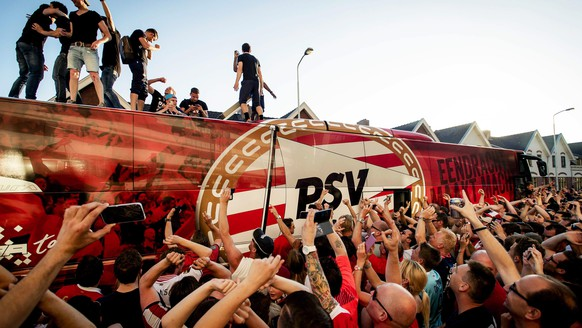 epa05295298 Fans of PSV Eindhoven celebrate as the PSV team bus arrives in Eindhoven, Netherlands, 08 May 2016, after PSV Eindhoven won the Dutch national soccer championship following the Dutch Eredivisie match against PEC Zwolle.  EPA/ROBIN VAN LONKHUIJSEN