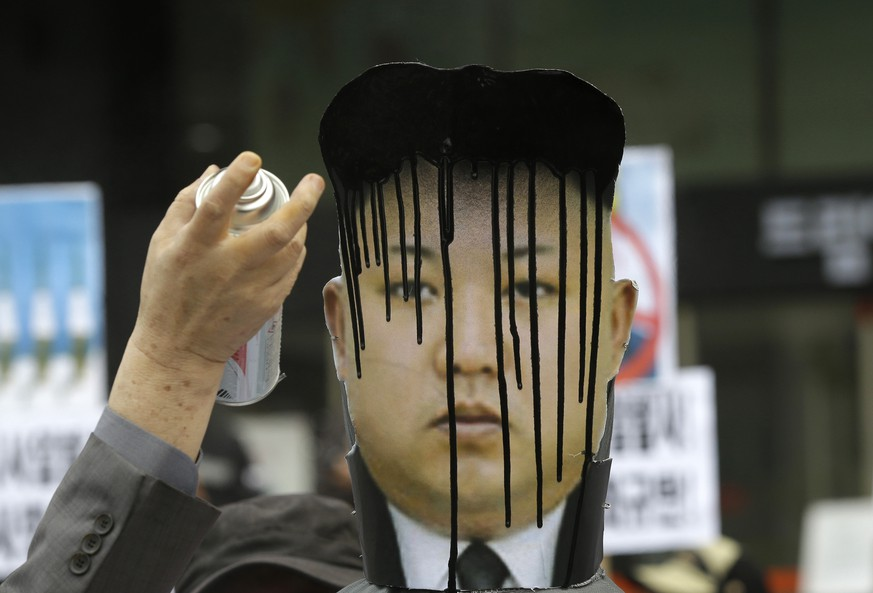 A picture of North Korean leader Kim Jong Un is sprayed by an anti-North Korean protester during an anti-North Korea rally against recent missile launches and provocative acts, on the birthday of its founder, Kim Il Sung, in Seoul, South Korea, Tuesday, April 15, 2014. (AP Photo/Lee Jin-man)